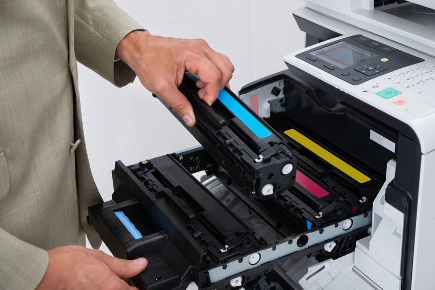 Cropped image of businessman fixing cartridge in photocopy machine at office